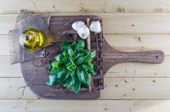 Albahaca, Olive Oil, y ajo frescos en tablero rústico Fotos de archivo