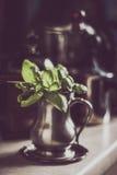 Albahaca verde en el tarro viejo del metal con los potes y las cacerolas borrosos Fotos de archivo