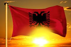 Albania flag weaving on the beautiful orange sunset with clouds background. Albania flag weaving on the beautiful orange sunset background stock photography