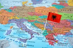 Albania map and flag pin. Albania paper flag pin on a map with neighbouring countries royalty free stock photos