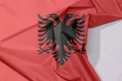 Albania tkaniny flaga zagniecenie z biel przestrzenią i krepa zdjęcie stock