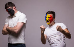 Albania vs Romania on grey background. Football fans of national teams demonstrate emotions: Albania – lose, Romania – win. Royalty Free Stock Photo