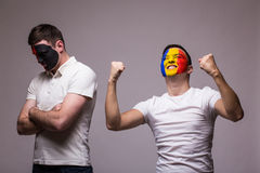 Albania vs Romania on grey background. Football fans of national teams demonstrate emotions: Albania – lose, Romania – win. Stock Images