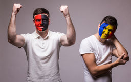 Albania vs Romania on grey background. Football fans of national teams demonstrate emotions: Albania – win, Romania – lose. Stock Images