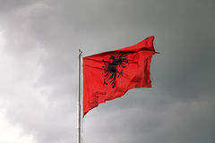 Albanian flag against a cloudy sky. The flag of Albania winding on a pole royalty free stock photography