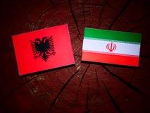 Albanian flag with Iranian flag on a tree stump isolated Stock Photo