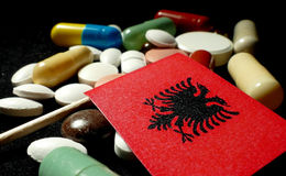 Albanian flag with lot of medical pills isolated on black Royalty Free Stock Image