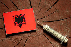 Albanian flag on a stump with syringe injecting money. In flag stock images