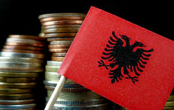 Albanian flag waving with stack of money coins. Macro stock photo