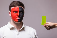 Albanian football fan of Albania national team get yellow card on grey background. Stock Photography