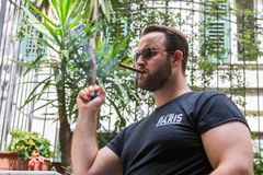 An albanian mafia guy is smoking a cigar and drinking. An albanian guy is dressed with a black t-shirt, blue jeans and black sunglasses. He is drinking beer in stock photography