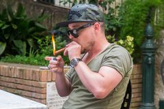 An albanian mafia guy is smoking a cigar and drinking. An albanian guy is dressed with a green and black t-shirt and blue jeans, green hat and black sunglasses royalty free stock photography