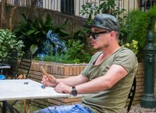 An albanian mafia guy is smoking a cigar and drinking. An albanian guy is dressed with a green and black t-shirt and blue jeans, green hat and black sunglasses royalty free stock images