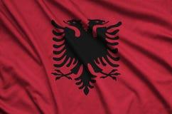 Albanien-Flagge wird auf einem Sportstoffgewebe mit vielen Falten dargestellt Sportteamfahne lizenzfreie stockfotos