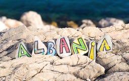 Albanien landsnamn som göras av målade stenar på havsbakgrund Royaltyfria Bilder