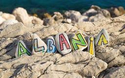 Albanien namn som göras av färgrika målade stenar, havsbakgrund Royaltyfri Bild