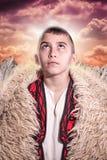 Albanisches Hochlandkind im traditionellen Kostüm, das oben zum Himmel schaut Lizenzfreie Stockfotografie