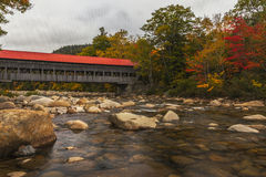Albany Covered Bridge with Fall Foliage. A covered bridge spans the Swift River, near Albany New Hampshire. The river is lined with trees displaying red, orange royalty free stock image