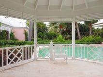 ALBANY, NASSAU BAHAMAS, LIPIEC - 21, 2018 Biała ławka, gazebo w basenie w ogródzie luksusowy kurort obrazy royalty free
