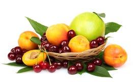 Albaricoque, cereza y manzana hermosos en una cesta Fotografía de archivo