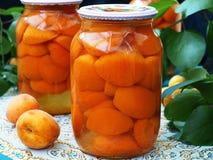 Albaricoques conservados en jarabe dulce en dos tarros en la tabla fotografía de archivo