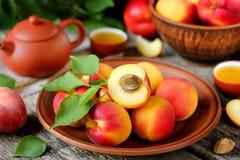 Albaricoques de la fruta fresca con las hojas en una tabla de madera Foto de archivo