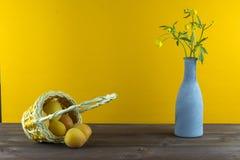 Albaricoques en la cesta Florero con los wildflowers en un fondo amarillo Humor del verano Fotografía de archivo libre de regalías