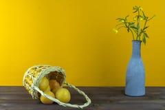 Albaricoques en la cesta Florero con los wildflowers en un fondo amarillo Humor del verano Fotografía de archivo