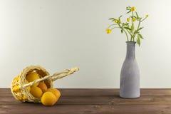 Albaricoques en la cesta Florero con los wildflowers en un fondo azul Humor del verano Fotos de archivo libres de regalías