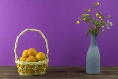 Albaricoques en la cesta Florero con los wildflowers en un fondo púrpura Humor del verano Fotografía de archivo libre de regalías