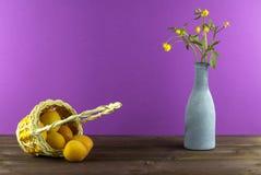 Albaricoques en la cesta Florero con los wildflowers en un fondo púrpura Humor del verano Imagenes de archivo