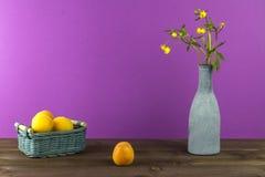 Albaricoques en la cesta Florero con los wildflowers en un fondo púrpura Humor del verano Imágenes de archivo libres de regalías