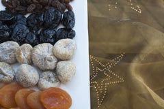 Albaricoques, higos y pasas con el mantel del oro en la Navidad Imágenes de archivo libres de regalías
