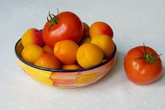 Albaricoques y tomates en un cuenco en el paño blanco Imagenes de archivo