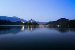 Albeggi nel lago sanguinato con i cieli blu, Slovenia Fotografia Stock
