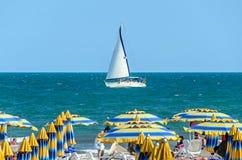 ALBENA, BULGARIA - JUNE 17, 2017: Wind boat yacht on blue Black Sea water near beach with tourists. ALBENA, BULGARIA - JUNE 17, 2017: Wind boat yacht on blue Stock Image