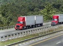 Alberi che circondano strada principale con i camion Immagine Stock