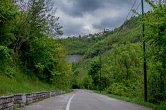 Alberi che circondano un giro della strada della montagna sotto il cielo epico con le nuvole immagine stock libera da diritti