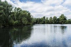 Alberi delle nuvole di riflessioni dell'acqua immagine stock libera da diritti