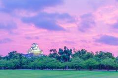 Alberi di erba del cielo di tramonto del castello di Himeji Jo distanti Fotografia Stock