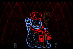 Alberi di Natale illuminati e del pupazzo di neve Fotografia Stock