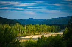 Alberi forestali del fiume e della montagna nei raggi del sol levante Fotografie Stock Libere da Diritti