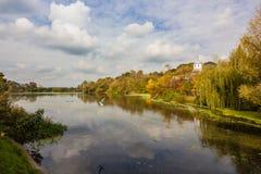 Alberi variopinti nella foresta di autunno vicino al lago ed alla chiesa in villaggio Fotografia Stock