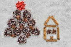 Albero dei biscotti di Natale vicino ad una casa fatta da cannella immagine stock
