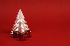 Albero del Libro Bianco e tre piccoli regali su fondo rosso Fotografie Stock Libere da Diritti