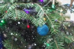 Albero del nuovo anno con la caduta della neve della cartolina di Natale del primo piano del giocattolo Fotografia Stock Libera da Diritti