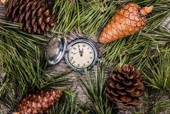 Albero di abete di Natale con i coni e l'orologio Fotografia Stock Libera da Diritti