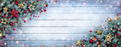 Albero di abete di Natale con le bagattelle ed i fiocchi di neve su di legno fotografie stock libere da diritti