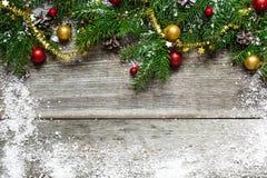 Albero di abete di Natale su fondo di legno con i fiocchi di neve Fotografia Stock
