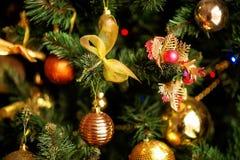 Albero di abete di Natale con le decorazioni dorate e gialle: archi e palle brillanti Concetto di vacanze invernali immagini stock